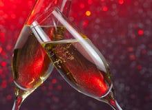 Les cannelures de Champagne avec de l'or bouillonne sur le fond de bokeh de lumière rouge Photo stock