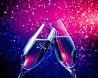Les cannelures de Champagne avec des bulles sur la teinte bleue allument le fond de bokeh Photographie stock