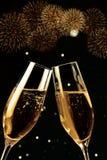 Les cannelures de Champagne avec les bulles d'or font des acclamations avec des feux d'artifice miroiter et noircir le fond Photographie stock