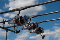 Les cannes à pêche avec des bobines sur une tente de cosse et de touriste de tige de système de support les vacances campent sur  Photographie stock libre de droits
