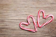 Les cannes de sucrerie de menthe poivrée au coeur forme sur le fond en bois Photo libre de droits