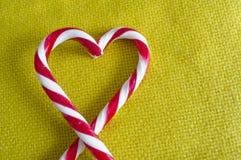 Les cannes de sucrerie de menthe poivrée au coeur forment sur le fond de textile Image stock