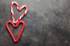 Les cannes de sucrerie de menthe poivrée au coeur forme sur le fond concret noir Fond de Noël Vue supérieure avec l'espace de cop Image libre de droits