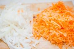 Les carottes et les oignons de coupe Raccords en caoutchouc frais Oignons frais Station service pour la salade Image stock