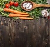 Les carottes fraîches avec les tomates-cerises, l'ail et le sel et le poivre en bois de vintage de cuillère l'ont coloré le dessu Image stock