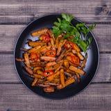Les carottes rôties dans le plat noir, se ferment  Photo stock