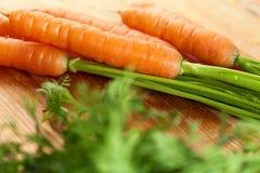 Les carottes se rassemblent sur le bois Images stock
