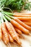 Les carottes se rassemblent sur le bois Photo stock