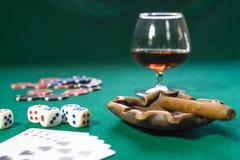 Les cartes, la matrice, les puces, un verre de cognac et le cigare sur une panne verte, le jeu est image libre de droits