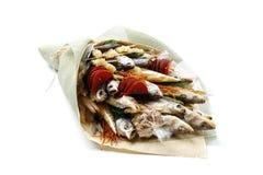 Les casse-cro?te, poissons secs, pistaches ont emball? sous forme de bouquet sur un fond blanc photos libres de droits