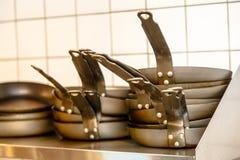 Les casseroles noires sont sur une étagère Photographie stock libre de droits