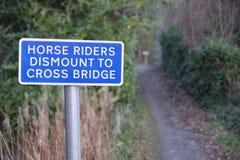 Les cavaliers de cheval démontent pour croiser le pont pour signer dans la campagne rurale R-U photographie stock libre de droits