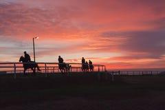 Les cavaliers de chevaux ont silhouetté des couleurs de ciel Images stock