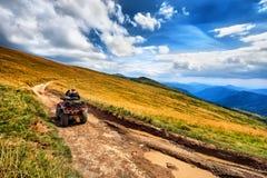 Les cavaliers de vélo de quadruple du panorama ATV sur la belle montagne aménagent en parc Photo stock