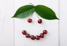Les cerises fraîches douces sourient sur le fond en bois blanc Images libres de droits