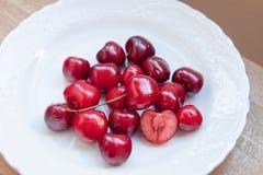 Les cerises rouges dans le plat photos stock