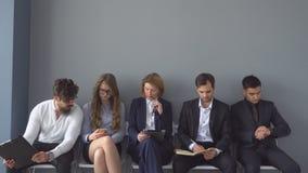 Les chômeurs s'attendent à des entrevues se reposant sur des chaises dans le couloir d'un immeuble de bureaux banque de vidéos