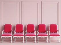 Les chaises classiques rouges se tiennent dans une salle rose vide avec des bâtis sur le mur Photographie stock libre de droits