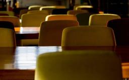 Les chaises colorées de bibliothèque et les bureaux en bois attendent des chercheurs pendant le matin photographie stock