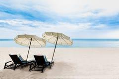 Les chaises de plage sur le sable blanc échouent avec le ciel bleu et le su nuageux Image stock