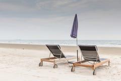 Les chaises et le parapluie de plage sur le sable blanc échouent avec la SK nuageuse Photos stock