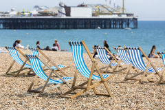 Les chaises longues rayées bleues et blanches sur Brighton échouent Photos stock