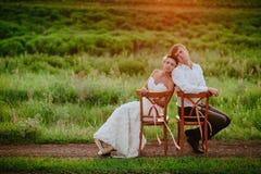 Les chaises se reposantes de baiser de beaux jeunes jeunes mariés dans le coucher du soleil s'allument Photographie stock libre de droits