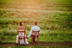 Les chaises se reposantes de baiser de beaux jeunes jeunes mariés dans le coucher du soleil s'allument Image stock