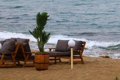 Les chaises se tiennent sur la plage à côté de la mer Image libre de droits