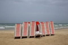 Les chaises se tiennent sur la plage à côté de la mer Photos stock