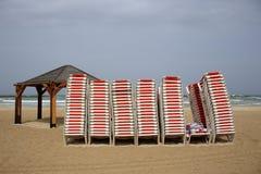 Les chaises se tiennent sur la plage à côté de la mer Photographie stock