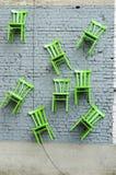 Les chaises sont accrochées sur le mur Chaises en bois sur un mur de briques Photo libre de droits