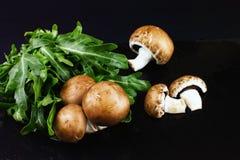Les champignons crus frais brunissent les champignons de paris et l'arugula vert sur un dar Photo stock