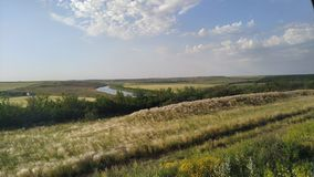 Les champs de Wast ont croisé par une rivière photographie stock libre de droits