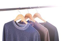 Les chandails d'un homme (T-shirts) avec des cintres ont isolé le blanc Photographie stock libre de droits