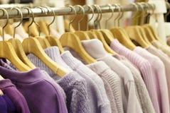 Les chandails tricotés multicolores accrochent sur des cintres dans le magasin photos stock