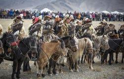 Les chasseurs mongols d'aigle de nomade ont aligné sur leurs chevaux images libres de droits