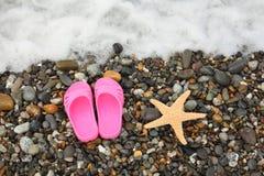 Les chaussons et les étoiles de mer sur des cailloux s'approchent de l'eau Image stock
