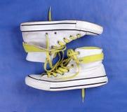 Les chaussures blanches avec la chaux lace sur le fond bleu Photographie stock libre de droits