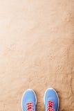 Les chaussures bleues de sports se sont étendues sur la plage de sable, tir de studio Photo libre de droits