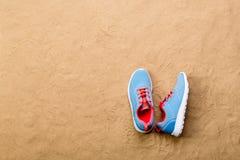 Les chaussures bleues de sports se sont étendues sur la plage de sable, tir de studio Photos libres de droits