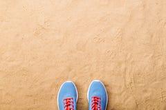 Les chaussures bleues de sports se sont étendues sur la plage de sable, tir de studio Photos stock