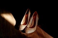 Les chaussures brun clair de jeune mariée se tiennent sur le plancher à la lumière du soleil sur le plancher en bois Image libre de droits
