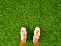 Les chaussures brunes molles d'espadrille de vintage d'usage de pieds de femme se tiennent sur le plancher d'herbe verte Photo stock