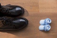 Les chaussures d'hommes ont mis vis-à-vis des chaussures de bébé images libres de droits