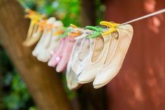 Les chaussures de ballet du ` s d'enfants sèchent sur une corde photographie stock libre de droits