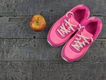 Les chaussures de course roses pour la forme physique classe au gymnase et à Apple mûr sur un plancher en bois Images stock
