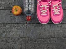 Les chaussures de course roses pour la forme physique classe au gymnase et à Apple mûr sur un plancher en bois Vue de ci-avant Images libres de droits