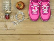 Les chaussures de course roses pour la forme physique classe au gymnase et à Apple mûr sur un plancher Vue de ci-avant Photographie stock