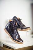 Les chaussures de cuir verni noires se trouvent sur l'étagère Image stock